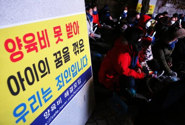 양육비 해결모임 회원들이 30일 서울 여의도 국회 앞에서 양육비 미지급 문제 해결을 촉구하는 촛불문화제를 열고 있다.