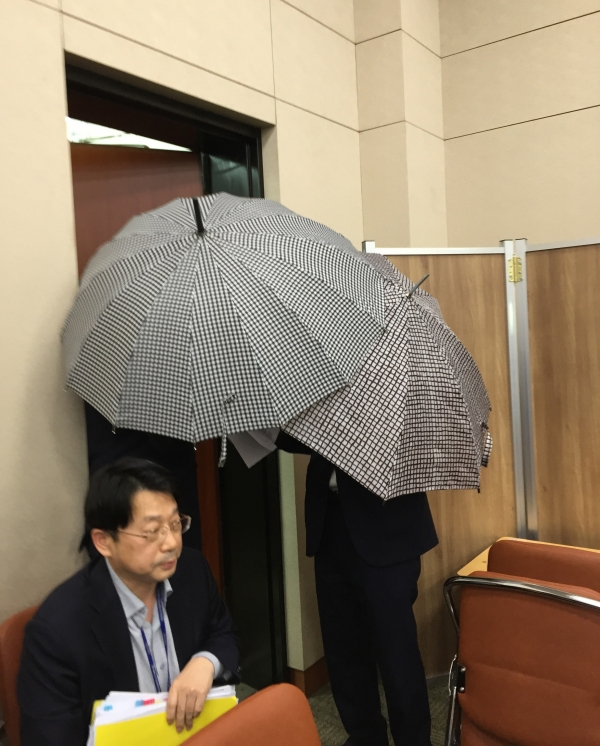 강서구 가정폭력 살인사건 유가족이 30일 국회에서 열린 여성가족위원회 국정감사장에 우산을 가린 채 참고인으로 출석하고 있다. ⓒ여성신문 진주원 기자
