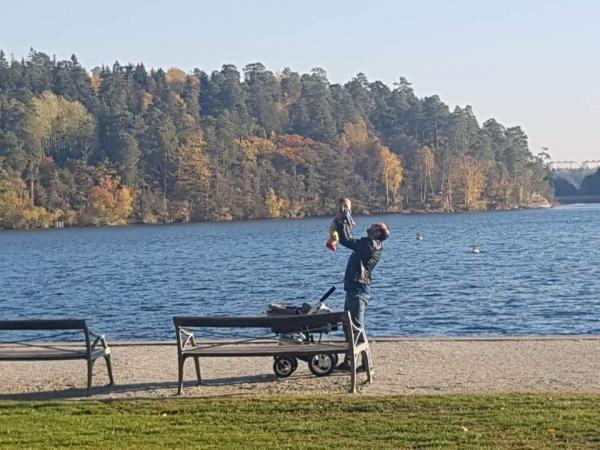 스웨덴 스톡홀름의 호숫가에서 한 남성이 아이를 돌보고 있다.