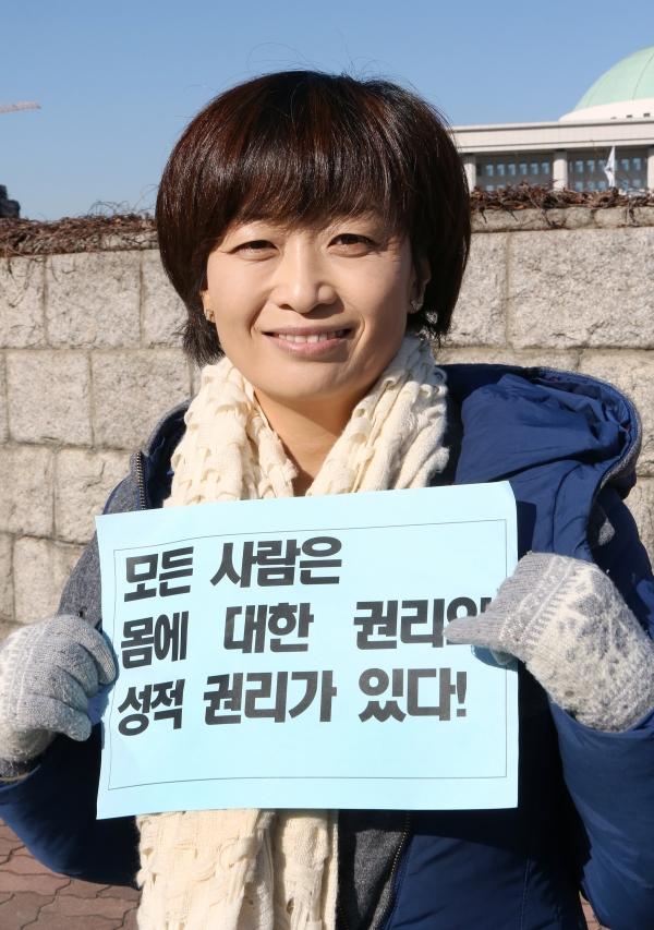 명숙 인권운동네트워크 바람 상임활동가가 10일 '페미니즘으로 다시 쓴 인권선언 발표' 기자회견 후 피켓을 들고 국회 정문 앞에 서 있다. ⓒ이정실 여성신문 사진기자