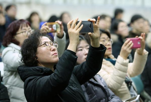 12일 서울 자양동 광진구청 대강당에서 열린 '2019학년도 정시 대학입시 설명회'에 참석한 학부모들이 핸드폰 카메라로 입시자료를 사진 찍고 있다.