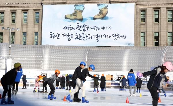 2일 서울광장 스케이트장에서 시민들이 스케이트를 즐기는 가운데 뒤로 새해를 맞아 새단장을 한 서울도서관 꿈새김판이 보이고 있다. ⓒ이정실 여성신문 사진기자