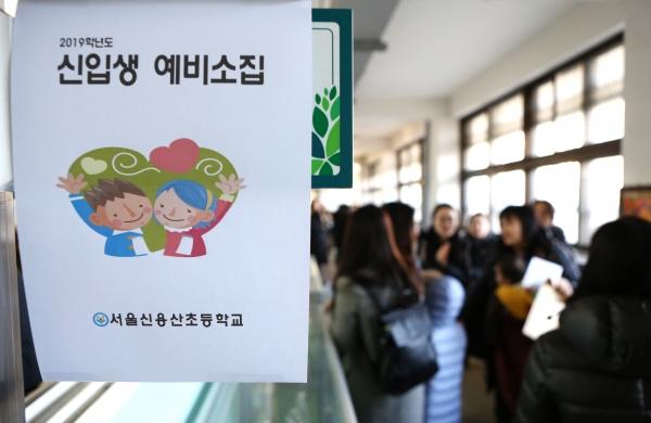 2019학년도 초등학교 입학 신입생 예비소집일인 8일 서울 용산구 신용산초등학교에서 학부모들이 입학등록을 하기위해 복도에 줄을 서 있다.
