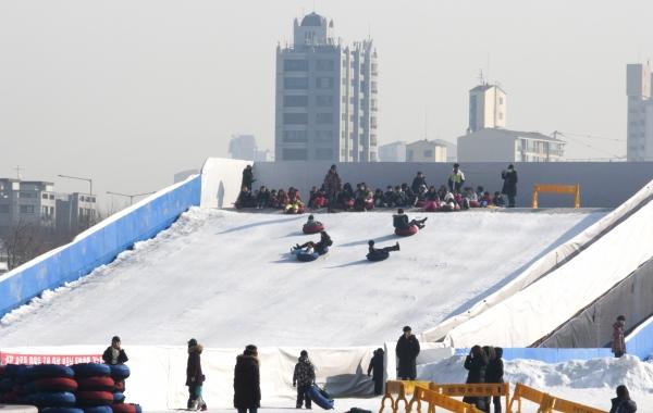 미세먼지 농도가 '나쁨'인 23일 서울 광진구 한강 뚝섬 눈썰매장을 찾은 시민들이 눈썰매를 타고 있다.