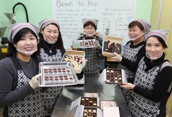 성수지앵 도시재생 협동조합원들이 24일 서울 성동구 성동 상생도시센터에서 천연재료로 만든 수제 초콜릿을 들어 보이고 있다. 12명의 성수지앵 조합원들은 쇼콜라티에 과정을 수료하고 1년간 수제 초콜릿 상품을 개발·생산하고 있다.