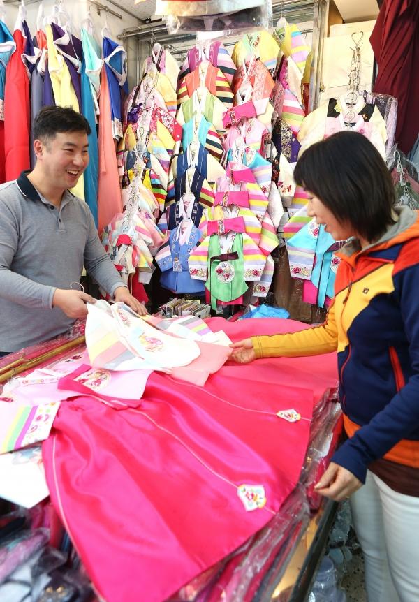 설날을 6일 앞둔 30일 서울 중구 남대문시장 한복 상가에 아이들의 설빔을 준비하려는 시민들이 한복을 살펴보고 있다.