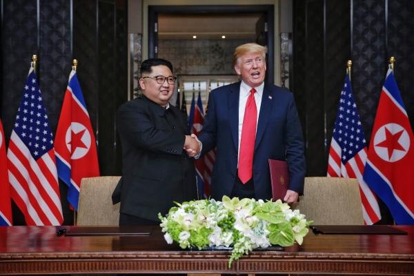 12일 김정은 북한 국무위원장과 도널드 트럼프 미국 대통령이 싱가포르 센토사섬 카펠라 호텔에서 북미정상회담 합의문 서명하고 있다. ⓒ뉴시스·여성신문