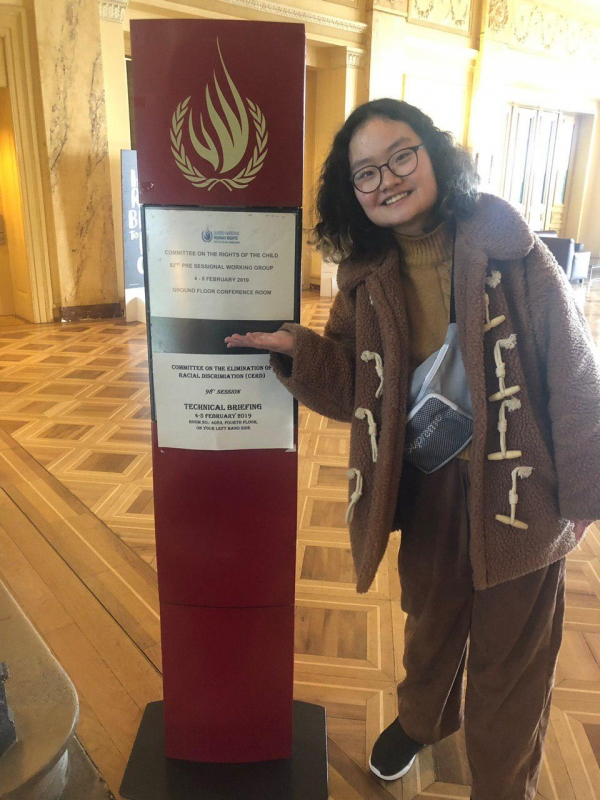 Wilson건물 내 UN아동권리위원회 사전심의 안내판을 가리키고 있는 청소년페미니즘모임의 양지혜 활동가.jpg ⓒ청소년페미니즘모임 제공