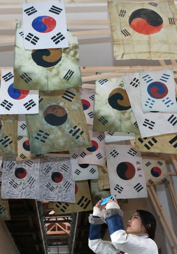 19일 서울 서대문형무소 역사과에서 열린 3.1운동과 임시정부 수립 100주년 특별전 '문화재에 깃든 100년 전 그날'에서 관람객이 3.1운동 때 사용됐던 다양한 태극기들의 사진을 찍고 있다.