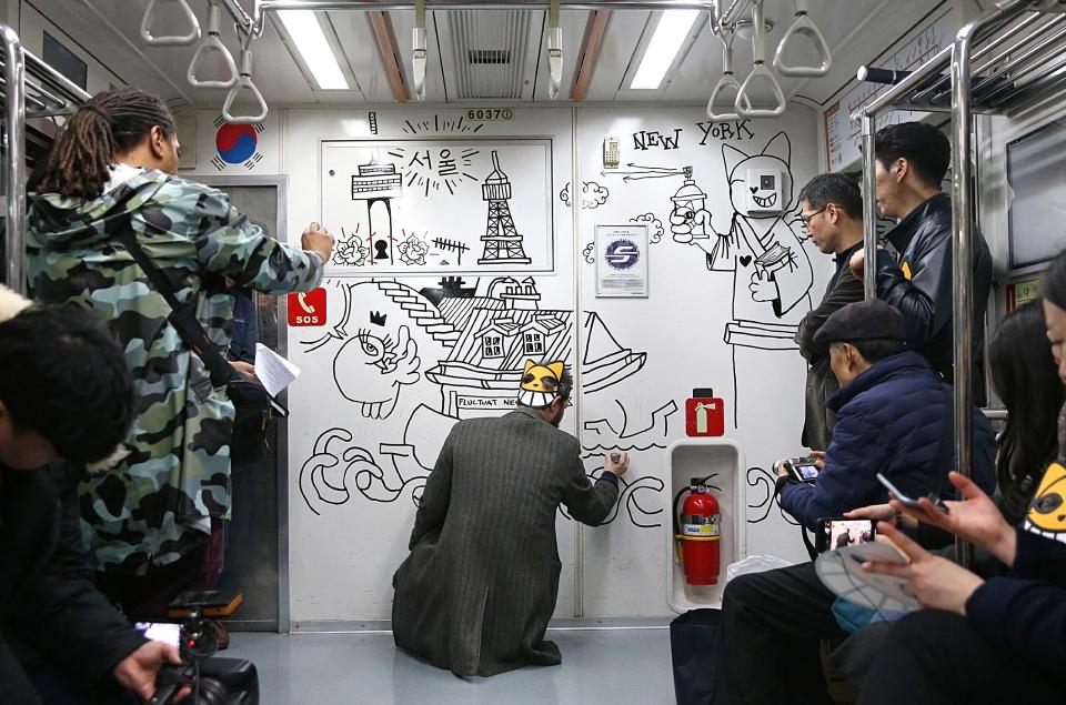 그래피티 거리예술가 토마 뷔유가 12일 서울 지하철 6호선 전동차 벽에 그의 대표 캐릭터인 '무슈샤 웃는 고양이' 그림을 그리는 행위예술을 하고 있다.