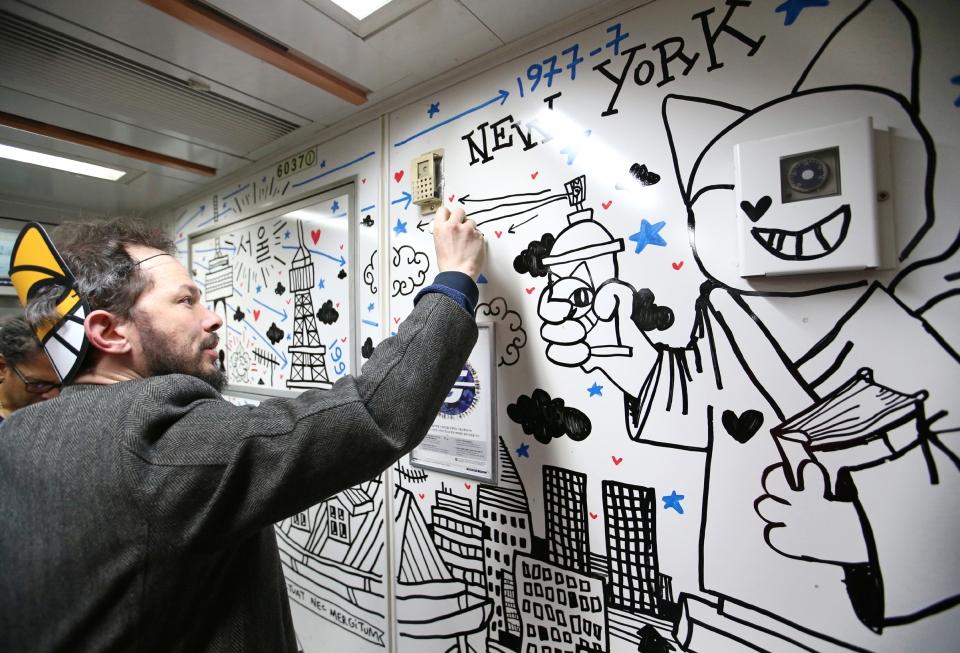 그래피티 행위예술가 토마 뷔유가 12일 서울 지하철 6호선 전동차 벽에 그의 대표 캐릭터인 '무슈샤 웃는 고양이' 그림을 그리는 행위예술을 하고 있다.