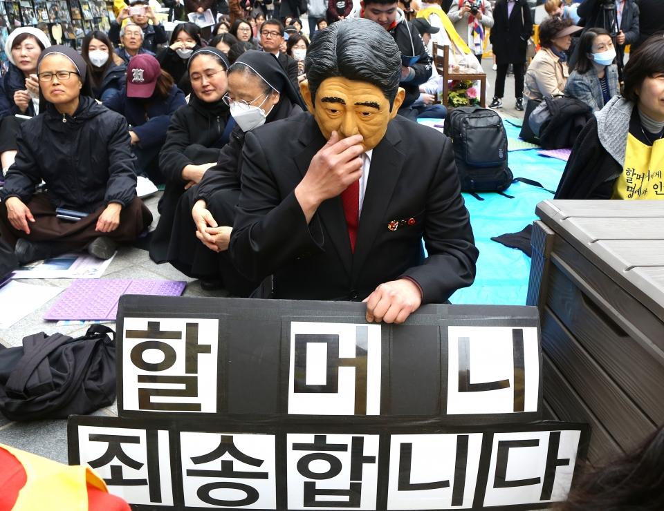 20일 서울 종로구 일본대사관 앞에서 제1379차 일본군성노예제 문제해결을 위한 정기 수요시위에 일본 아베 총리의 가면을 쓴 참가자가 '할머니 죄송합니다' 팻말을 들고 있다.