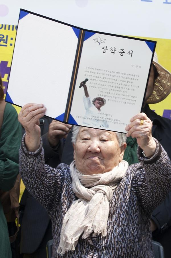 길원옥 할머니가 17일 서울 종로구 주한 일본대사관 앞에서 열린 제1383차 일본군성노예제문제해결을 위한 정기 수요시위에서 시민사회단체 활동가 대학생 자녀들에게 수여하는 '김복동 장학금'을 수여하며 장학증서를 들어 보였다.