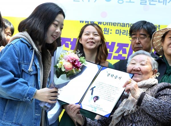 길원옥 할머니가 17일 서울 종로구 주한 일본대사관 앞에서 열린 제1383차 정기 수요시위에서 고(故) 김복동님의 뜻을 기리는 '김복동 장학금'을 시민사회단체 활동가 대학생 자녀들에게 전달했다.