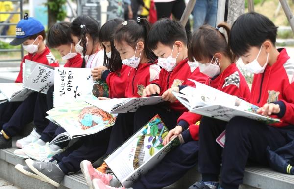 23일 서울 마포구 경의선책거리에서 열린 '세계 책과 저작권의 날' 기념행사에서 어린이들이 미세먼지 마스크를 쓰고 책을 읽고 있다.