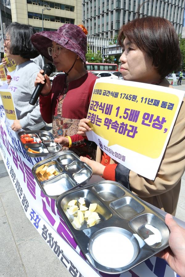 정치하는엄마들이 2일 서울 광화문 광장에서 '어린이집 급간식비 인상촉구 기자회견'을 열어 참가자들이 어린이집 1일 급간식비인 1745원어치의 식료품을 들고 있다.