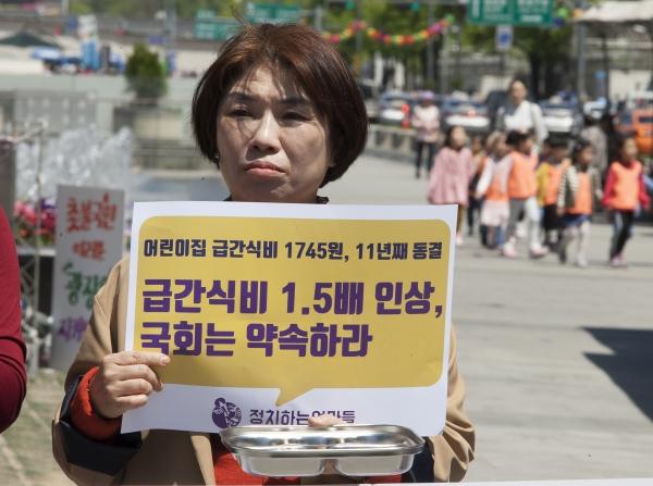 정치하는엄마들이 2일 서울 광화문 광장에서 '어린이집 급간식비 인상촉구 기자회견'을 열고 있는 뒷쪽으로 가운데 어린이집 원아들이 지나가고 있다.