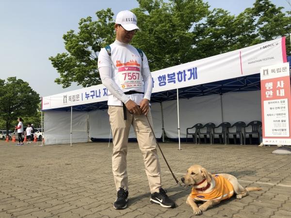 노란 안내견 조끼를 입은 레트리버 '코지'와 함께 대회에 참가한 김경우(47) (주)트러스트텍스타일 대표이사. ⓒ여성신문 진혜민