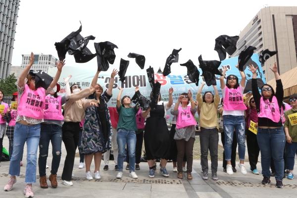 17일 서울 광화문광장에서 열린 제3회 성별임금격차 해소를 위한 '임금차별타파의 날' 기자회견에서 참가자들이 성차별적 구조를 고발하는 문구가 적힌 천을 찢어 하늘 높이 던지는 퍼포먼스를 하고 있다.