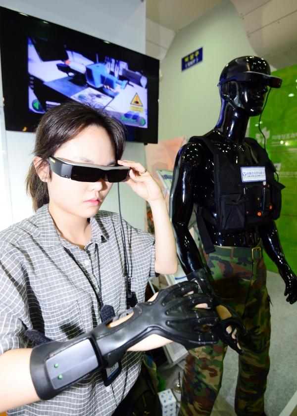 'K-ICT WEEK in BUSAN' 행사장을 찾은 한 여성이 다중센서융합형 웨어러블 증강현실 플랫폼을 체험하고 있다. ⓒ뉴시스·여성신문