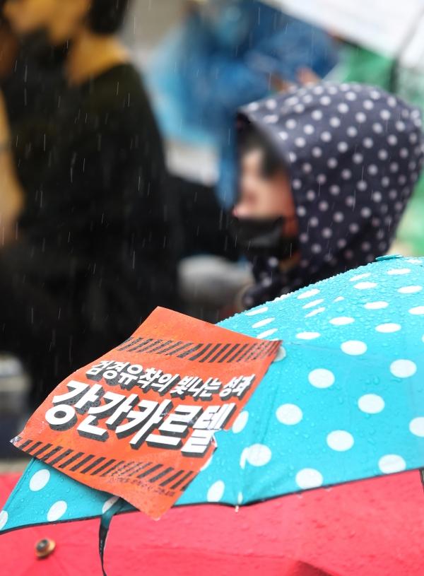 19일 서울 종로구 청와대 사랑채 앞에서 '강간카르텔 유착수사 규탄시위'가 열려 참가들이 피켓을 들고 구호를 외치고 있다.