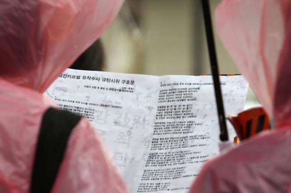 19일 서울 종로구 청와대 사랑채 앞에서 '강간카르텔 유착수사 규탄시위'가 열려 참가들이 빗속에 주최측에서 나눠준 유인물을 보며 구호를 외치고 있다. ⓒ이정실 여성신문 사진기자