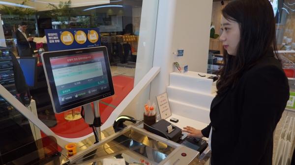 세븐일레븐 시그니처 매장에서 한 고객이 정맥인증 결제 서비스인 '핸드페이' 방식으로 결제하고 있다. ⓒ세븐일레븐