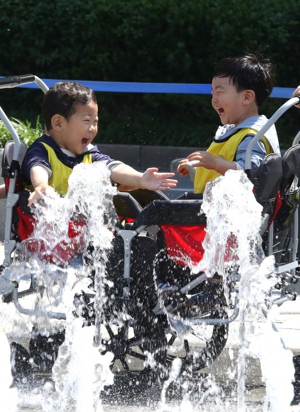 서울의 한낮 최고 기온이 25도를 기록하며 전국이 초여름 날씨를 보인 22일 유모차를 타고 서울 광화문광장을 지나가는 어린이들이 바닥분수에서 내뿜는 물줄기를 보며 즐거워하고 있다.