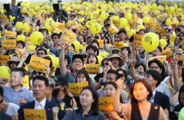 18일 오후 서울 광화문광장에서 열린 고 노무현 대통령 서거 10주기 시민문화제에서 참가자들이 '새로운 노무현'이 적힌 손팻말을 흔들고 있다.