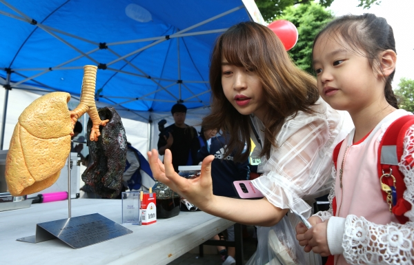 28일 서울 구로구 동구로초등학교에서 청소년 흡연예방 캠페인이 열려 학부모가 자녀에게 사람의 폐 모형을 보며 흡연에 대해 설명하고 있다.
