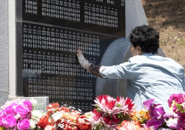 '호국보훈의 달' 6월을 앞두고 29일 서울 동작구 국립서울현충원을 찾은 유가족이 부부위패를 모신 묘역의 묘비 앞에서 고인의 넋을 추모하고 있다.
