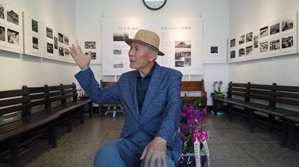 김재도 탑리버스터미널 대표가 터미널 내부에 전시된 사진에 대해 설명하고 있다. 김 대표는 버스터미널을 만든 아버지의 뒤를 이어 65년간 버스터미널을 지키고 있다.
