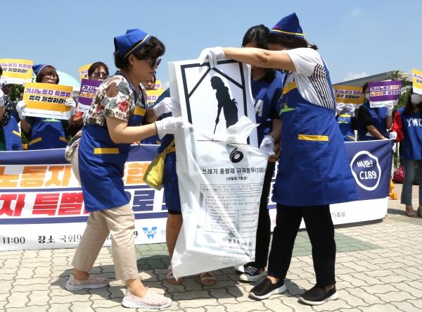 '국제가사노동자의 날'을 앞둔 12일 서울 여의도 국회 정문 앞에서 열린 가사노동자들의 노동권 보장을 촉구하는 기자회견에서 노동권을 인정받지 못하는 그림자 노동을 부셔 버리는 퍼포먼스를 하고 있다.