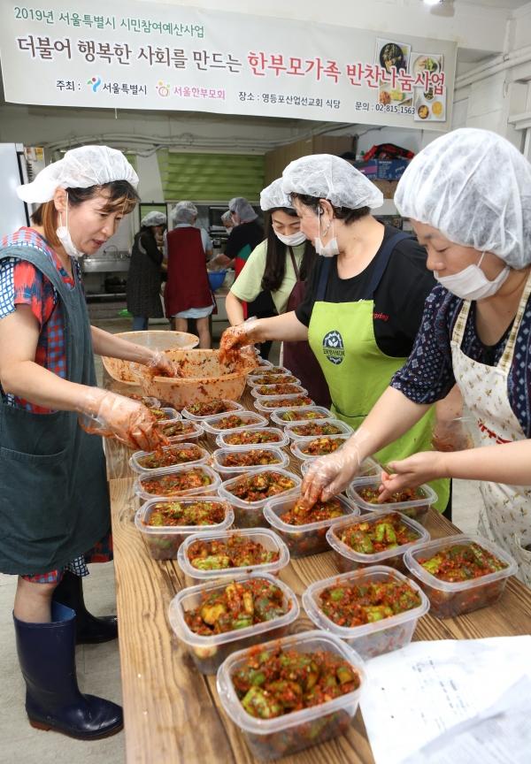 서울한부모회가 15일 서울 당산동 영등포산업선교회 식당에서 첫 번째 '한부모가족 반찬나눔'행사를 열어 회원들이 오이소박이를 반찬통에 담고 있다.