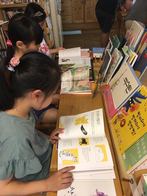 '숲속 작은 책방'을 찾은 어린이들이 동화책을 보고 있다. ©숲속 작은 책방