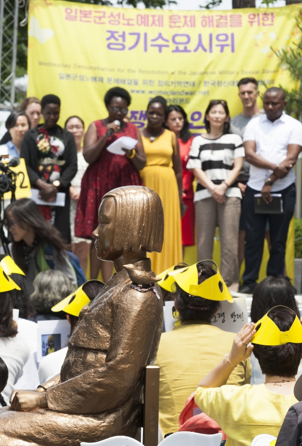 19일 서울 종로구 일본대사관 앞에서 열린 '일본군성노예제 문제해결을 위한 1392차 정기 수요시위'에 '2019 세계 전시성폭력 추방의 날' 행사 참석을 위해 한국을 방문한 우간다 전시성폭력 피해자 단체 관계자들과 교사워크샵 참석자들이 참석해 연대발언을 하고 있다.