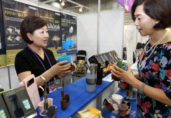 이인실 한국여성발명협회 회장이 22일 경기 일산 킨텍스 제2전시장에서 열린 '2019 여성발명왕엑스포'에서 ㈜뉴디아아이엔씨의 서정옥 대표에게 차아네-와이드 컵홀더 제품에 대한 설명을 듣고 있다.