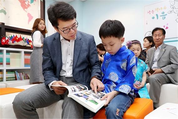 정원오 성동구청장과 중국 전통의상 치파오를 입은 어린이가 함께 그림책을 보고 있다. ⓒ성동구청