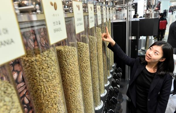 커피 콩을 바라보는 한 여성. ⓒ뉴시스·여성신문
