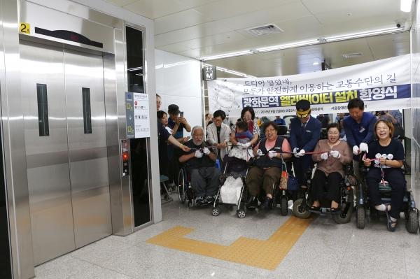서울장애인차별철폐연대 회원들이 광화문역 엘리베이터 완공 축하하며 테이프 커팅식을 하고 있다.