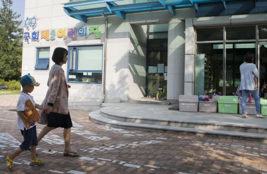한 여성이 어린이집에 아이를 데려다주고 있다. 정부가 15일 보육체계와 돌봄 서비스를 맞벌이 부부 중심으로 개편하겠다고 밝혔다. ⓒ이정실 여성신문 사진기자