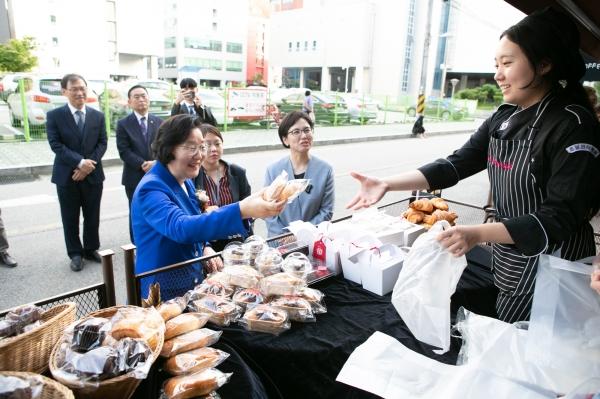 이정옥 여성부 장관이 학생 직접 만든 빵을 구매하고 있다.