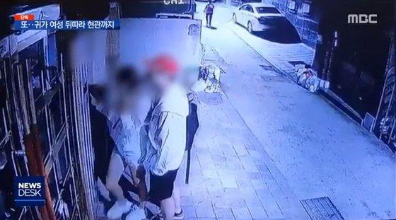 A씨가 여성을 뒤쫓아온 후 공동 현관 앞에서 비밀번호를 누르는 모습을 지켜보는 장면. ⓒMBC 뉴스데스크 캡처