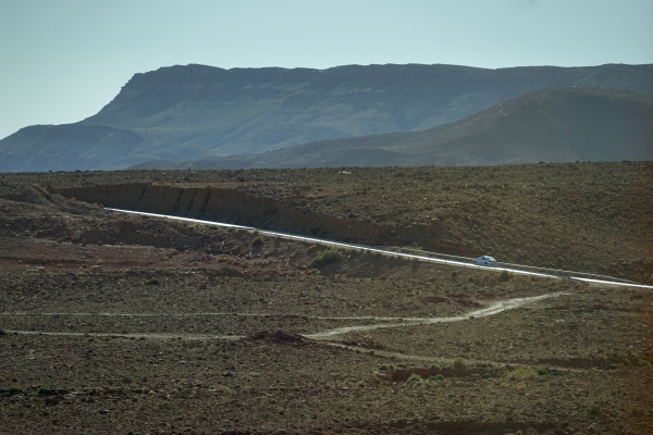 사하라 사막 입구 도시로 달려가는 길에 만난 작은 언덕. 쭉 뻗은 빛나는 길을 자동차가 빠르게 올라간다. (모로코 에르푸드 인근). 사진_조현주