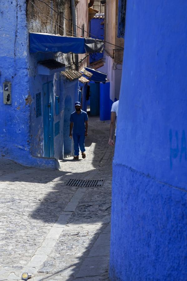 빛이 가득한 푸른색 골목길에 파란색 옷과 흰 옷 입은 남자가 스쳐 지나 간다. 사진_조현주