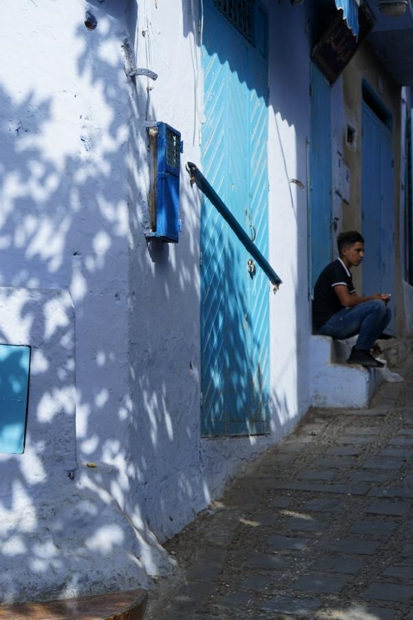 나무잎 그림자가 아른거리는 골목에 어린 소년이 하염없이 앉아 있다. 사진_조현주