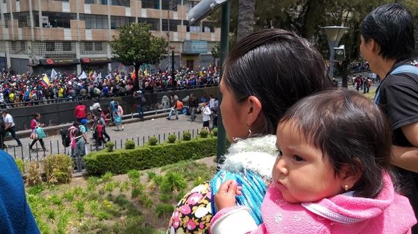 아기를 업은 에콰도르 선주민 여성이 시위 현장을 바라보고 있다. ©BBC