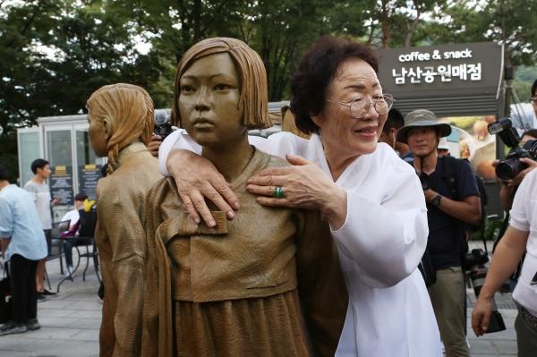 정면을 응시하며 손을 맞잡고 있는 세명의 소녀(한국, 중국, 필리핀)를 '위안부' 피해자 이용수 할머니가 끌어안았다.