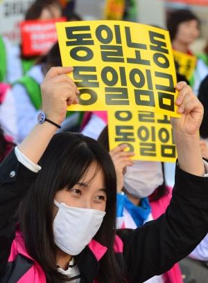 여성 비정규직 노동자들이 성별임금격차를 의미하는 '동일노동 동일임금' 피켓을 들고 시위를 벌이고 있다. (사진은 해당 기사와 관련없음) ⓒ뉴시스·여성신문