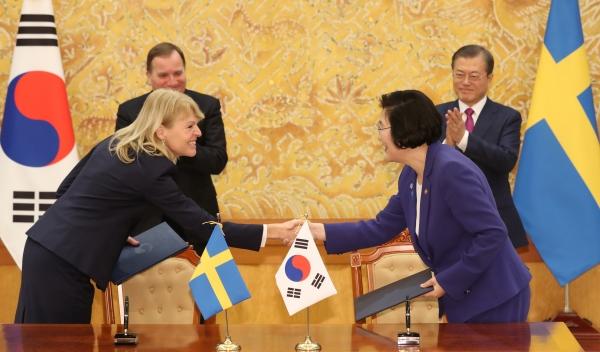 이정옥 여성가족부 장관과 안나 할바리 스웨덴 통상장관이 18일 오후 청와대 본관에서 문재인 대통령과 스테판 뢰벤 스웨덴 총리가 지켜보는 가운데 성평등 분야 양해각서를 체결하고 있다. ⓒ뉴시스·여성신문